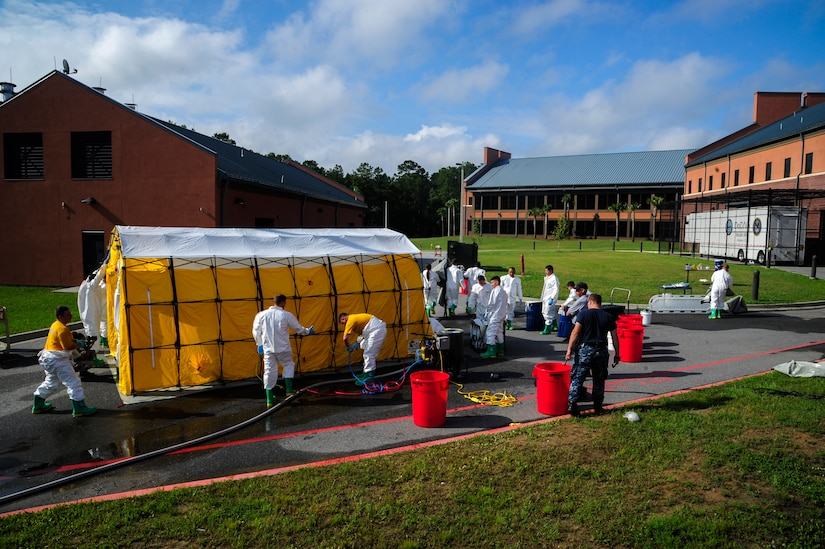 """Sailors from the Naval Health Clinic Charleston practice assembling a decontamination tent before executing their final timed exercise June 21, 2013, at Joint Base Charleston - Weapons Station, S.C. The NHCC team participated in a First Receivers Operation Training course designed to educate U.S. Navy Medical First Receivers on life-saving skills required to triage, initiate field treatment, decontaminate and save victims from Chemical, Biological, Radiological/Nuclear, or Hazardous Material. The 16-hour course consisted of one, eight-hour day of class lecture and a second eight-hour day of """"hands-on"""" teamwork training to include a final """"timed"""" exercise. (U.S. Air Force photo/Staff Sgt. Rasheen Douglas)"""