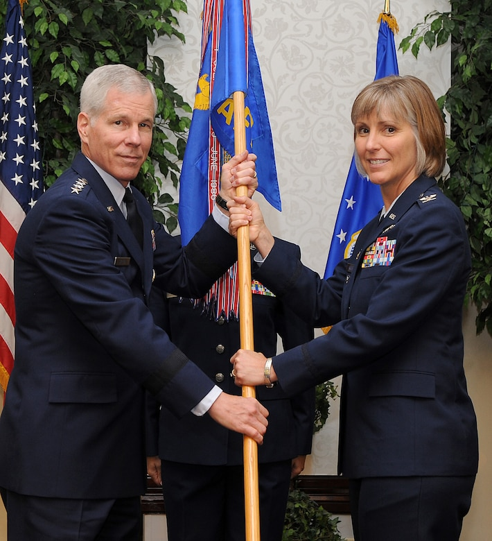 Gen. William Shelton, Air Force Space Command commander, presents the Air Force Network Intergration Center guidon to Col. Amy Arwood signifying to start of Arwood's command of AFNIC during a ceremony June 26, 2013 at Scott Air Force Base, Ill.  Arwood arrived from Edwards Air Force Base, Calif., where she served as the Director of Staff of the 412th Test Wing. (U.S. Air Force photo/Senior Airman Divine Cox)