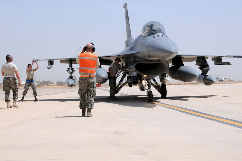 U.S. Air Force Tech. Sgt. Michael Bilberry, a crew chief with the 169th Aircraft Maintenance Squadron at McEntire Joint National Guard Base, South Carolina Air National Guard, marshals an F-16 Fighting Falcon from the 157th Fighter Squadron, that landed at Joint Base Balad (JBB), Iraq, May 16, 2010.  Staff Sgt. Kenneth Monroe (left), Airman 1st Class Lyla Rayer and Staff Sgt. Leonard Gajewsky (center) with the 169th Aircraft Maintenance Squadron, work to quickly de-arm the aircraft.  Personnel from McEntire are deployed to JBB on an Air Expeditionary Force rotation to take over the Air Tasking Order for the 332nd Air Expeditionary Wing.(U.S. Air National Guard photo by Tech. Sgt. Caycee Watson/Released)