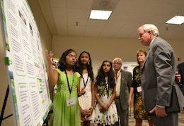 """Seventh-grader Divya Mereddy explains the project of her team, """"STEM Ninjas,"""" to Lloyd Caldwell, director of military programs for the U.S. Army Corps of Engineers, with teammates Rachana Subbanna and Sneha Thandra. The Corps' director of human resources, Sue Engelhardt, and Fidel Rodriguez look on. The STEM Ninjas won first place on June 21, 2013, for their grade in the 11th Annual eCYBERMISSION National Judging and Education Event."""