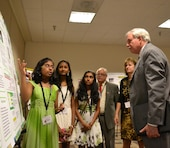 "Seventh-grader Divya Mereddy explains the project of her team, ""STEM Ninjas,"" to Lloyd Caldwell, director of military programs for the U.S. Army Corps of Engineers, with teammates Rachana Subbanna and Sneha Thandra. The Corps' director of human resources, Sue Engelhardt, and Fidel Rodriguez look on. The STEM Ninjas won first place on June 21, 2013, for their grade in the 11th Annual eCYBERMISSION National Judging and Education Event."
