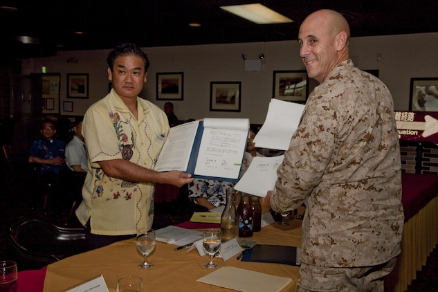 Mayor Atsushi Sakima, and Col. James G. Flynn display their signed copies of a bilateral agreement June 26 on Marine Corps Air Station Futenma. The agreement specifies evacuation methods for Okinawa residents to transit through the air station in the event of a natural disaster and provides for evacuation drills to maintain preparedness. Sakima is the mayor of Ginowan City, and Flynn is the commanding officer of MCAS Futenma. (U.S. Marine Corps photo by Lance Cpl. Elizabeth A. Case/Released)