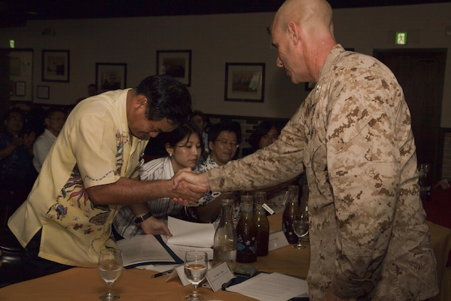 """Mayor Atsushi Sakima, left, shakes hands with Col. James G. Flynn after signing a bilateral agreement June 26 on Marine Corps Air Station Futenma. The agreement, which specifies evacuation procedures in the event of a natural disaster, is a result of thorough collaboration between Ginowan City and MCAS Futenma officials and signifies the importance that the city and air station place on mutual safety and cooperation. """"The joint signing of this document recognizes the importance our communities place on preparing for a natural disaster that may jeopardize the safety of our citizens,"""" said Flynn. """"I am confident that in working together we will undoubtedly protect the lives of countless men, women, children, old and young, faced by a tsunami or other catastrophe. It is my wish that we continue to find opportunities where we can work together on important issues affecting our citizens."""" Sakima is the mayor of Ginowan City, and Flynn is the commanding officer of MCAS Futenma. (U.S. Marine Corps photo by Lance Cpl. Elizabeth A. Case/Released)"""