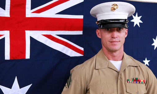 Sgt. Ian Polhamus, squad leader, 3rd Platoon, Lima Company, 3rd Battalion, 3rd Marine Regiment, Marine Rotational Force - Darwin, poses in front of an Australian flag, here, June 27. Polhamus lived Down Under for seven years. He said Australia feels like his home away from home.