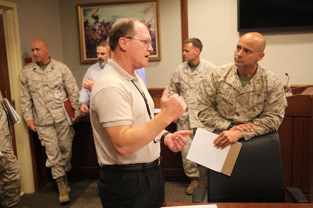 James Carothers, representative from Marine Forces North, and Maj. Jason Burkett, Headquarters Marine Corps' Manpower and Reserve Affairs representative, discuss operational logistics after the conclusion of the first Marine Corps lead Defense Support of Civil Authorities working group at the Marine Force Reserve and MARFORNORTH headquarters, June 20. Representatives from major U.S. Marine Corps headquarters based in the U.S., gathered in support of DSCA to discuss and synchronize natural disaster response efforts and capabilities, review current operational requirements and prepare for the upcoming hurricane and wildland fire season.(Official U.S. Marine Corps photo by Cpl. Fenton Reese)