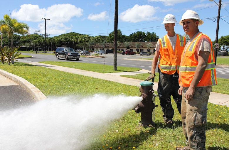 Tech. Sgt. Benjamin M. Johnson, left, job foreman and plumber with the 647th Civil Engineering Squadron and Senior Airman Tito M. Irlas, right, a plumber with the 624th CES, survey the parking lot of the shoppette on Kuntz Avenue while using a fire hydrant to flush out any debris or dirt that may have gotten into a main water line while they were fixing it, Joint Base Pearl Harbor-Hickam, Hawaii, June 27, 2013. Irlas, a reservist, performing his two-week annual tour for training, works with active duty craftmen such as Johnson, a former RED HORSE member, who has more than 11 years of experience as a plumber. (U.S. Air Force photo by Tech. Sgt. Phyllis E. Keith)
