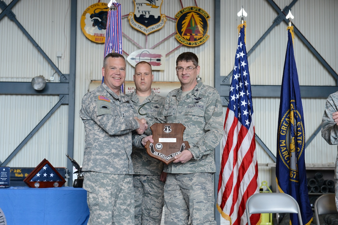 Maj. Gen. Judd Lyons, Nebraska National Giuard's adjutant general, awards Col. Keith Schell, commander of the 155th Air Refueling Wing with an Outstanding Unit award for fiscal year 2012 at the Hometown Heroes Salute ceremony April 6, 2013, at the Nebraska National Guard air base, Lincoln, Neb. The purpose of the ceremony is to honor family members and unit members who had deployed, for their sacrifices made.