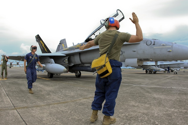 Lance Cpl. James C. Dye, an aircraft ordnance technician with Marine All-Weather Fighter Attack Squadron 242, gives orders through hand and arms signals to arm an F/A-18D Hornet for flight at Clark Air Base, Republic of the Philippines, June 11 during Exercise Haribon Tempest 2013. The purpose of Haribon Tempest 2013 is to increase the proficiency, interoperability and combined capabilities of Marine Aircraft Group 12 and the Philippine Air Force.