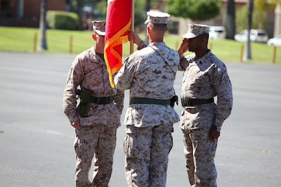 Lieutenant Col. Christian D. Richardson, center, outgoing commanding officer, 1st Maintenance Battalion, Combat Logistics Regiment 15, 1st Marine Logistics Group, passes on his battalion's battle colors to the oncoming commanding officer, Lt. Col. Mark T. Donar,. left, during a change of command ceremony aboard Camp Pendleton, Calif., June 27, 2013. Richardson has served as the commanding officer since June 17, 2011.