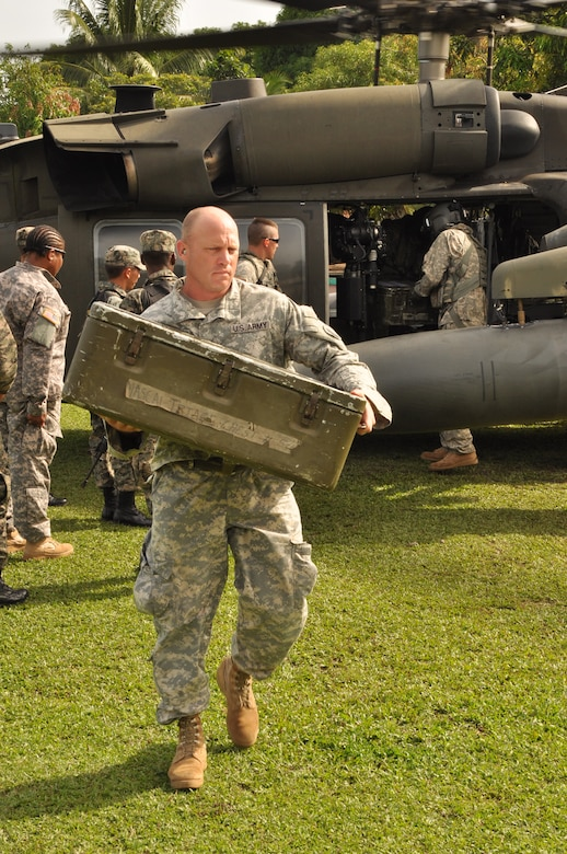 U.S. Army Maj. Stephen Poe, Medical readiness training exercise officer-in-charge, carries medical supplies from a Utility Helicopter-60 during a MEDRETE held in the remote region of Bara Patuca, Gracias a Dios, June 25-26, 2013. JTF-Bravo conducts MEDRETEs throughout Central America each year in support of U.S. Southern Command's humanitarian assistance and disaster relief programs in order to strengthen civil-military cooperation between the United States and nations in the region. In coordination with the Offices of Security Cooperation and partner nation Department of Health Officials in all seven Central American countries, JTF- Bravo treated more than 11,000 patients, last year.