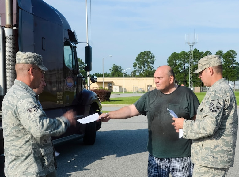 Senior Airman Dennis Tippens, left, and Master Sgt. Joel Furlough, 116th Civil Engineer Squadron, Georgia Air National Guard, take possession of two route clearance kits from a truck driver at Robins Air Force Base, Ga., June 27, 2013.  The civil engineering arm of the 116th Air Control Wing will use the kits, consisting of multi-purpose Kubota tractors, when called upon to quickly respond to disasters in their region.  The equipment gives the unit the capability to clear debris in the area of a disaster so emergency operations personnel can respond. (U.S. Air National Guard photo by Capt. Pamela Stauffer/Released)