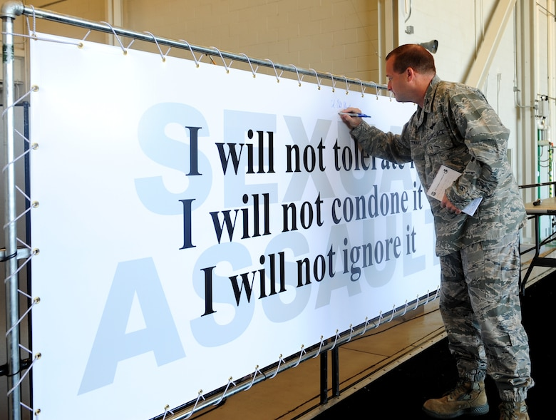 Col. Phil Stewart, 9th Reconnaissance Wing commander, signs a banner pledging to stop sexual assault during a sexual assault prevention and response brief at Beale Air Force Base, Calif., June 26, 2013. All of Team Beale was given the opportunity to sign the pledge. (U.S. Air Force photo by Airman 1st Class Bobby Cummings/Released)