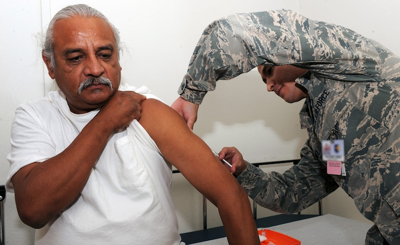U.S. Air Force Tech. Sgt. Daniel Gomez, 355th Medical Operations Squadron aerospace medicine technician, gives a patient a vaccine shot at the immunizations clinic at Davis-Monthan Air Force Base, Ariz., June 27, 2013. The355th MDOS provides medical care to maximize the health and welfare of our current and retired warriors and their family members, both in theater and at home. (U.S. Air Force photo by Senior Airman Christine Griffiths/Released)