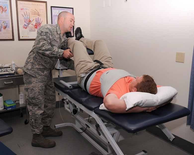 U.S. Air Force Tech. Sgt. Gregory Dorner, 355th Medical Operations Squadron physical therapist, situates a patient on the traction machine at the physical theraphy clinic at Davis-Monthan Air Force Base, Ariz., June 27, 2013. The traction machine is used to create a space between the vertebrae and stretch the back to relieve any pain on the patient.  (U.S. Air Force photo by Senior Airman Christine Griffiths/Released)