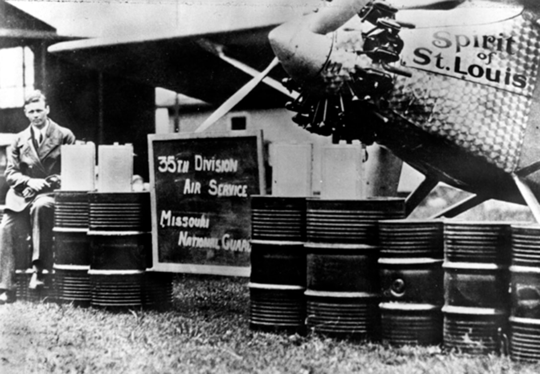 """Aviator Capt. Charles Lindbergh, 110th Observation Squadron, 35th Division, Missouri National Guard (now 131st Bomb Wing, Missouri Air National Guard) poses beside the """"Spirit of Saint Louis"""" at Robertson Field with a representation of how much fuel was required to complete his historic 33 1/2 solo flight from New York to Paris in the """"Spirit of Saint Louis"""" on May 21, 1927.  He had to seek permission from his commanders at the 110th to make this flight.  (131st Bomb Wing file photo/RELEASED)"""