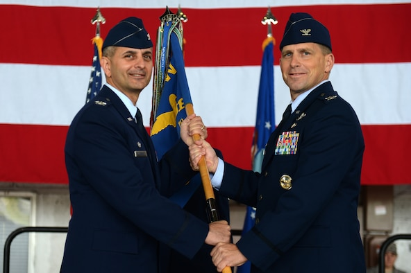 SPANGDAHLEM AIR BASE, Germany -- U.S. Air Force Col. Robert Winkler, 52nd Operations Group commander, right, receives the 52nd guidon from U.S. Air Force Col. David Julazadeh, 52nd Fighter Wing commander, during a change of command ceremony June 28, 2013. Winkler accepted command from U.S. Air Force Col. David Lyons, the outgoing 52nd OG commander. A change of command is a military tradition that represents a formal transfer of authority and responsibility for a unit from one commanding officer to another. (U.S. Air Force photo by Airman 1st Class Gustavo Castillo/Released)