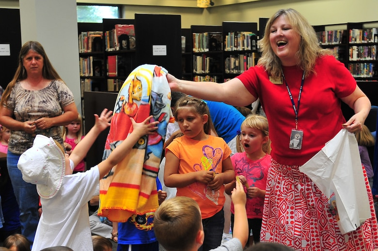 Kimberly Webb, 4th Force Support Squadron library director, hands out a summer reading program blanket as a raffle prize at the library at Seymour Johnson Air Force Base, N.C., June 25, 2013. More than 100 children, from newborn to the age of six, attended the summer travel safety-themed puppet show as a part of the library's summer reading program. (U.S. Air Force photo by Senior Airman Aubrey White/Released)