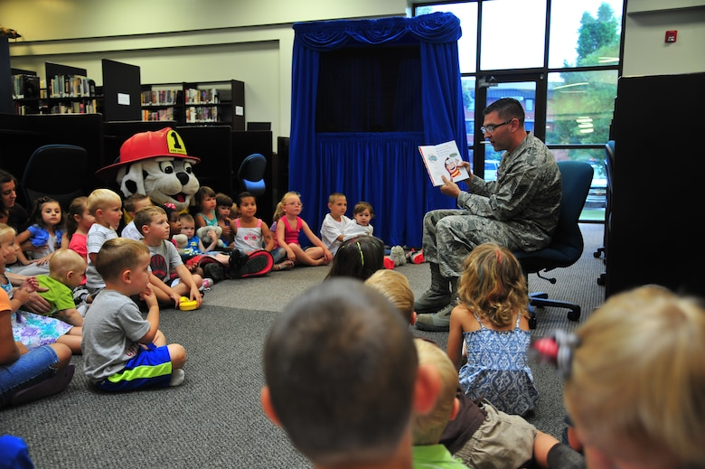 """U.S. Air Force Tech. Sgt. Brandon Sanderson, 4th Civil Engineer Squadron NCO in charge of fire prevention, reads a story to children attending the library's summer reading program at Seymour Johnson Air Force Base, N.C., June 25, 2013. This year's summer reading program theme is """"Have Book – Will Travel."""" (U.S. Air Force photo by Senior Airman Aubrey White/Released)"""