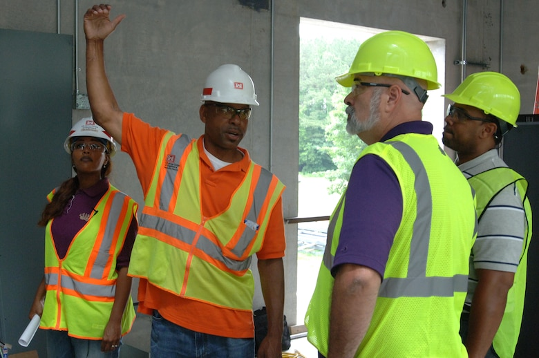 Construction Engineering Technician Victory Young (Second from Left) and Project Engineer Debbie Dowell, U.S. Army Corps of Engineers Nashville District Mid Cumberland Construction Office, talk about ongoing construction of a new navigation lock operators building at Cheatham Dam with Victor Bright (Right), history teacher, and Harold Cunningham, construction teacher, during a tour June 6, 2013.  The Cane Ridge High School teachers were participating in an externship with the Corps to develop project based learning curriculum.