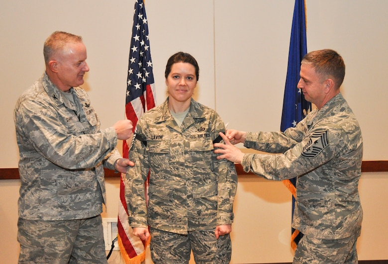 """Master Sgt. Jill LaVoie, 460th Space Wing Public Affairs superintendent, gets her newest stripes """"tacked on"""" by Col. Dan Dant, 460th SW commander, and Chief Master Sgt. William Ward, 460th SW command chief, during a promotion release party Feb. 28, 2013, at the Leadership Development Center on Buckley Air Force Base, Colo. LaVoie is one of six Team Buckley senior master sergeants selects. (U.S Air Force photo by Staff Sgt. Nicholas Rau/Released)"""