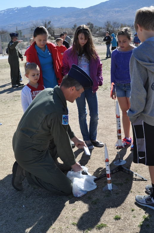 Lt. Col. Dan Jones, 612th Air and Space Operations Center Space Director, prepares to shoot-off a rocket during a demonstration at Tanque Verde Elementary School in Tucson, Ariz., March 1. Airmen from 12th Air Force (Air Forces Southern) gave 5th grade students a lesson on space operations (launch operations, weather support, launch control centers and the importance of launch observation and recovery) during their visit. (USAF photo by Master Sgt. Kelly Ogden/Released).