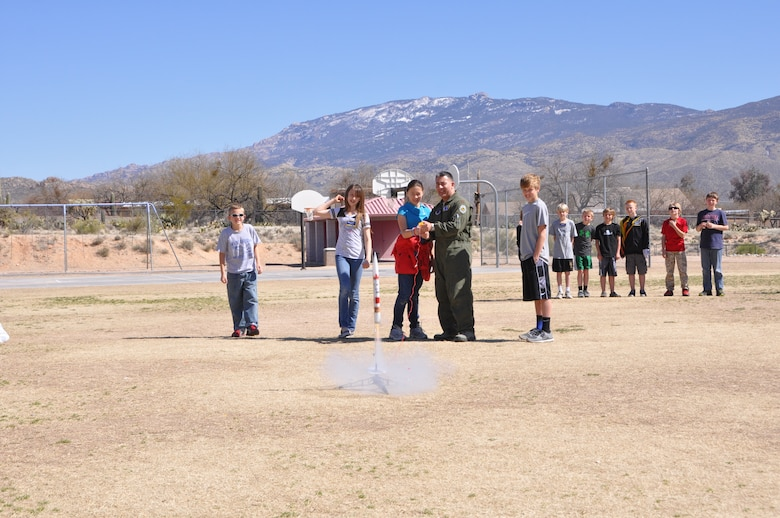 Maj. Andre Benitez, 612th Air and Space Operations Center, shoots off a rocket during a demonstration at Tanque Verde Elementary School in Tucson, Ariz., March 1. Airmen from 12th Air Force (Air Forces Southern) gave 5th grade students a lesson on space operations (launch operations, weather support, launch control centers and the importance of launch observation and recovery) during their visit. (USAF photo by Lt. Col. Dan Jones/Released).