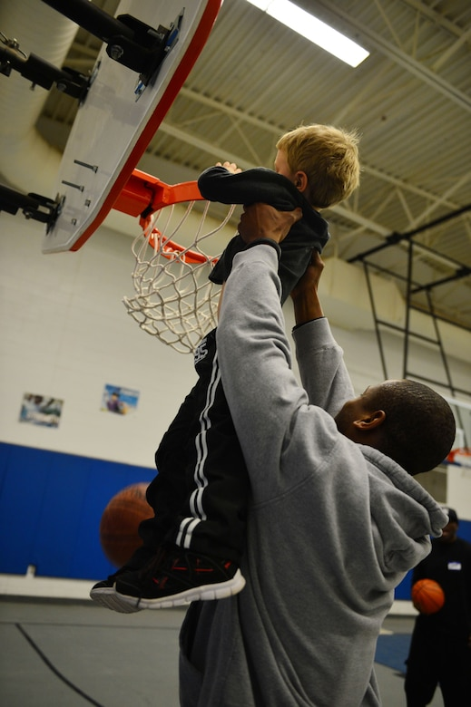 U.S. Air Force Staff Sgt. James Dexter, 27th Special Operations Civil Engineer Squadron, lifts a child up so he can dunk a basketball through the hoop at a youth basketball clinic held in the Youth Center at Cannon Air Force Base, N.M., Feb. 26, 2013. Cannon's men's varsity basketball team hosted a youth basketball clinic for children, ages 6-11, to teach them standard fundamentals of the game. (U.S. Air Force photo/Airman 1st Class Eboni Reece)