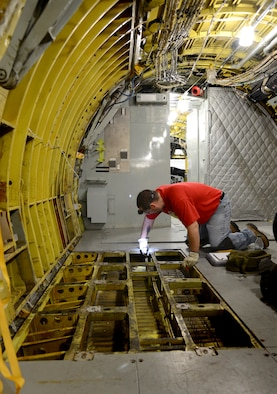 Robert Martin, a sheet metal mechanic with the 564th Aircraft Maintenance Squadron, examines the floors on a KC-135 Stratotanker in the Inspection Dock of Bldg. 2283. When all of the fabric in the walls, ceilings and floors of the aircraft is completely taken out, it will be thoroughly sprayed with a Corrosion Preventative Compound. This step will take approximately three days, compared to being scattered throughout the entirety of the aircraft's maintenance schedule. (Air Force photos by Kelly White)