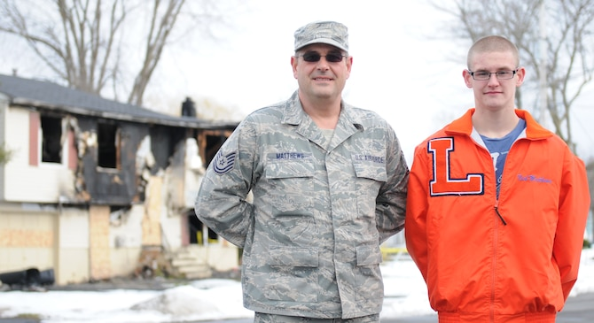 New York Air National Guard Tech. Sgt. Brian Matthews (left) of the 174th Attack Wing Communications Squadron, along with his son Nicolas, stand in front of the home in Clay, New York where they rescued several neighbors who were trapped inside during a major house fire the night of February 13, 2013. Tech. Sgt. Matthews, who is stationed at Hancock Field Air National Guard Base, took immediate action after hearing a smoke alarm while walking his dog. (NYANG Photo By Senior Airman Duane Morgan/Released)