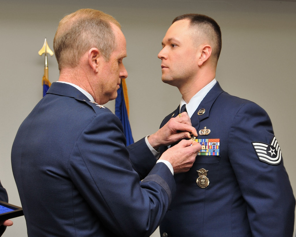 Maj. Gen. Donald P. Dunbar, adjutant general of Wisconsin, presents the Purple Heart to Tech. Sgt. Cristian A. Bennett, 115th Fighter Wing assistant program security manager, during a ceremony in Madison, Wis., Feb. 4. Bennett received the medal for injuries received when his Humvee was struck by an improvised explosive device during a security escort mission in Iraq on Feb. 24, 2006.