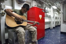 Corporal Bernard Vu, field radio operator, 2nd Platoon, Battery B, Battalion Landing Team 3/5, 15th Marine Expeditionary Unit, practices playing guitar aboard USS Rushmore, Feb. 27. While away, servicemembers find many ways to pass time while improving themselves and others physically, mentally and professionally.The 15th MEU is deployed as part of the Peleliu Amphibious Ready Group as a U.S. Central Command theater reserve force, providing support for maritime security operations and theater security cooperation efforts in the U.S. 5th Fleet area of responsibility. Vu, 20, is from Lincoln, Neb. (U.S. Marine Corps photo by Cpl. Timothy R. Childers/ Released)