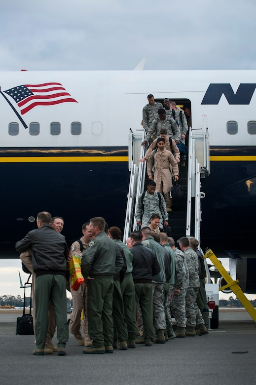 Returning members of the 14th Airlift Squadron exit the commercial plane which flew them home during the 14th AS redeployment March 3, 2013, at Joint Base Charleston - Air Base, S.C. More than 100 Airmen from the 14th AS returned home from a 120-day deployment to Southwest Asia. (U.S. Air Force photo/ Senior Airman George Goslin)