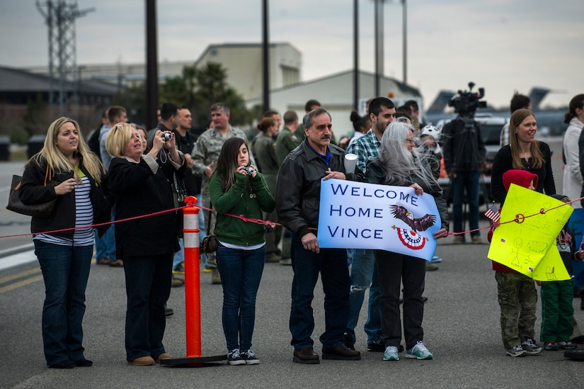 The family of Airman 1st Class Vince Denisi, 14th Airlift Squadron loadmaster, waits for him to exit the plane during the 14th AS re-deployment March 3, 2013, at Joint Base Charleston - Air Base, S.C. More than 100 Airmen from the 14th AS returned home from a 120-day deployment to Southwest Asia. (U.S. Air Force photo/ Senior Airman George Goslin)