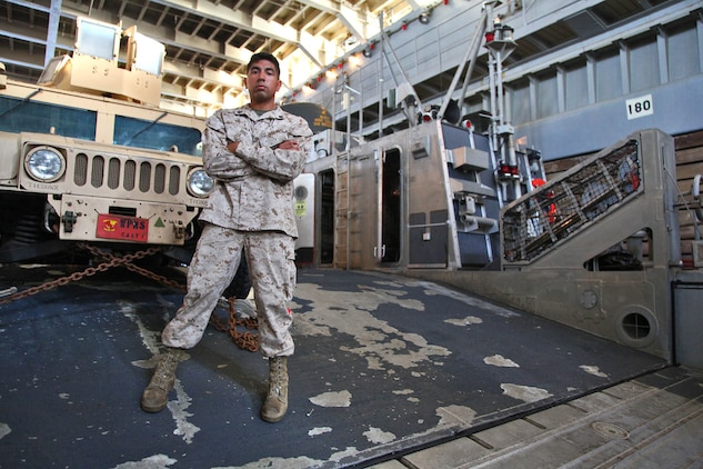 Sergeant Joshua V. Ruiz, landing support specialist, Transportation Support Detachment, Combat Logistics Battalion 15, 15th Marine Expeditionary Unit, poses for a photo in the well-deck of the USS Rushmore, Feb. 19. The 15th MEU is deployed as part of the Peleliu Amphibious Ready Group as a U.S. Central Command theater reserve force, providing support for maritime security operations and theater security cooperation efforts in the U.S. 5th Fleet area of responsibility. (U.S. Marine Corps photo by Cpl. Timothy R. Childers/ Released)