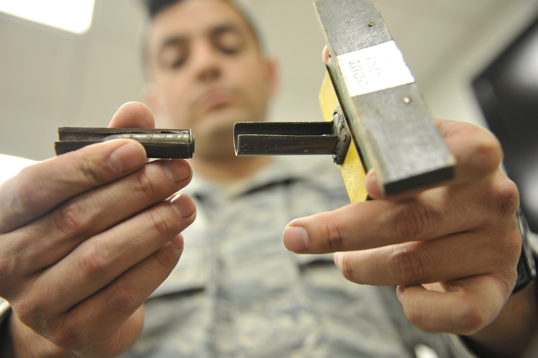 WHITEMAN AIR FORCE BASE, Mo. -- Airman 1st Class Fernando Aguilera, 509th Civil Engineer Squadron Explosive Ordinance Disposal team member, examines at a land mine, Feb. 27. This mine is designed as a defensive weapon to explode when stepped on. (U.S. Air Force photo/Airman 1st Class Keenan Berry) (Released)