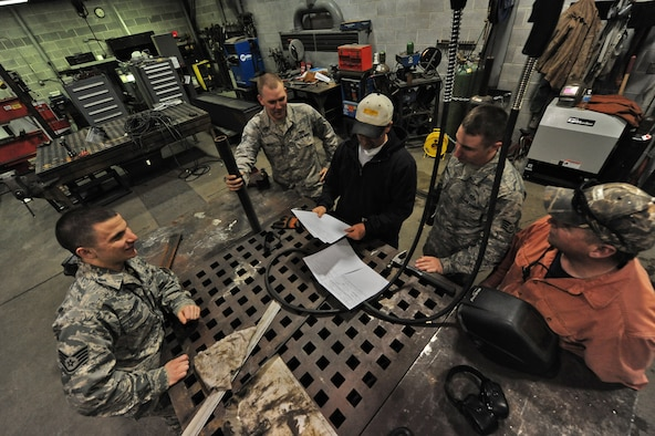 WHITEMAN AIR FORCE BASE, Mo. -- Members from the 509th Civil Engineer Squadron structures flight discuss procedures for snow plow repair, Feb. 27. The flight constructs, remodels, repairs and maintains 861 base facilities totaling over 4.8 million square feet. (U.S. Air Force photo/Staff Sgt. Nick Wilson) (Released)