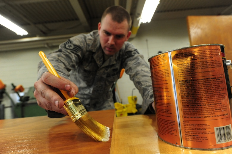 WHITEMAN AIR FORCE BASE, Mo. -- Staff Sgt. Adam Boyd, 509th Civil Engineer Squadron structural supervisor, polishes a wooden door with polyurethane, Feb. 27. The polish provides a durable protective finish that guards against the absorption of moisture. (U.S. Air Force photo/Staff Sgt. Nick Wilson) (Released)
