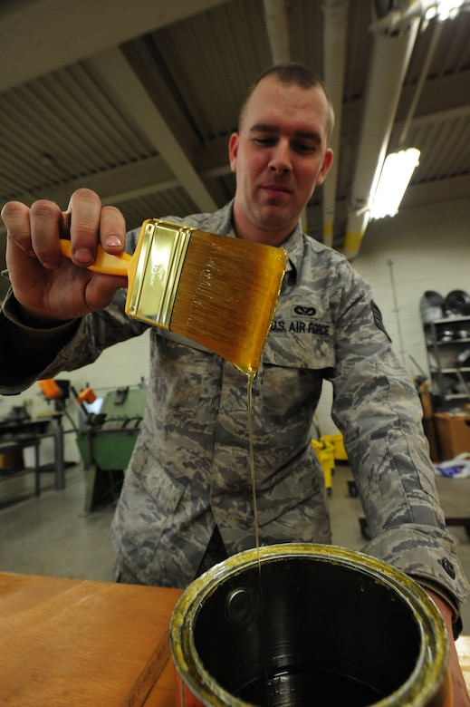 WHITEMAN AIR FORCE BASE, Mo. -- Staff Sgt. Adam Boyd, 509th Civil Engineer Squadron structural supervisor, dips a brush in polyurethane before polishing a wooden door, Feb. 27. The polyurethane prevents moisture from absorbing into the wood. (U.S. Air Force photo/Staff Sgt. Nick Wilson) (Released)