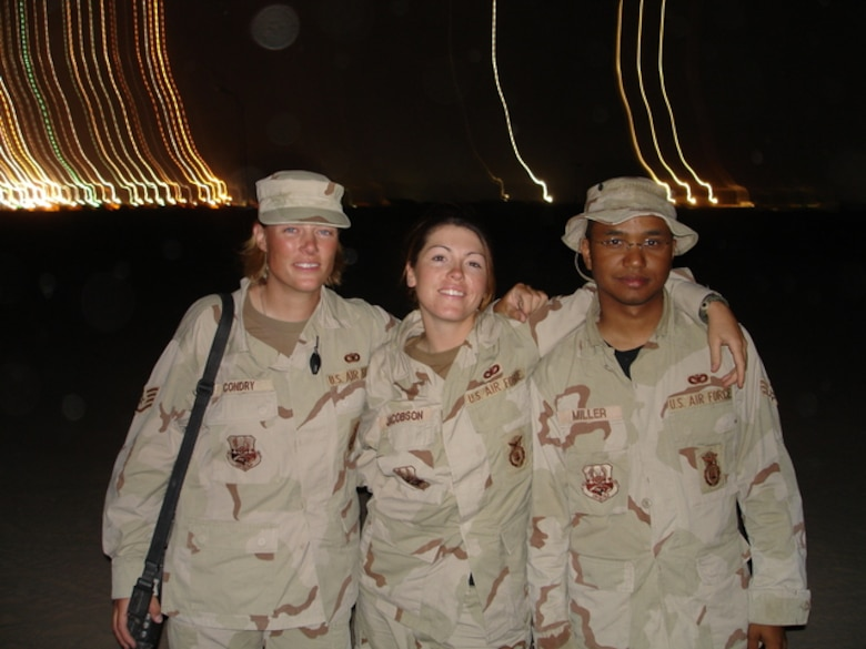 Airman 1st Class Elizabeth Jacobson (middle), smiles with two of her fellow Airmen, during her deployment to Iraq in 2005. Jacobson was killed on Sept. 28, 2008, when a roadside bomb detonated near her vehicle on a convoy delivering supplied to Camp Bucca, Iraq. Jacobson was a security forces member with the 17th Security Forces Squadron at Goodfellow Air Force Base, Texas. (Courtesy photo)