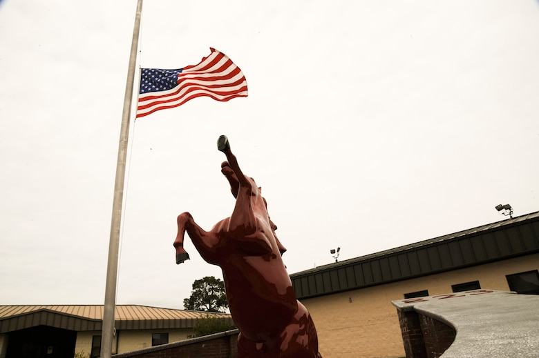 """The 823rd RED HORSE Squadron flag stands at half-staff in honor of retired Brig. Gen. William Thomas Meredith.  The founding father or RED HORSE is responsible for the signature red hats.  """"In the late 70's, he believed that there was a need to distinguish [RED HORSE Airmen] from regular civil engineering units and have their own identifying mark,"""" said Staff Sgt. John Reece, pavements and construction operator of 823rd RHS.  (U.S. Air Force Photo by Airman 1st Class Benjamin D. Kim)"""