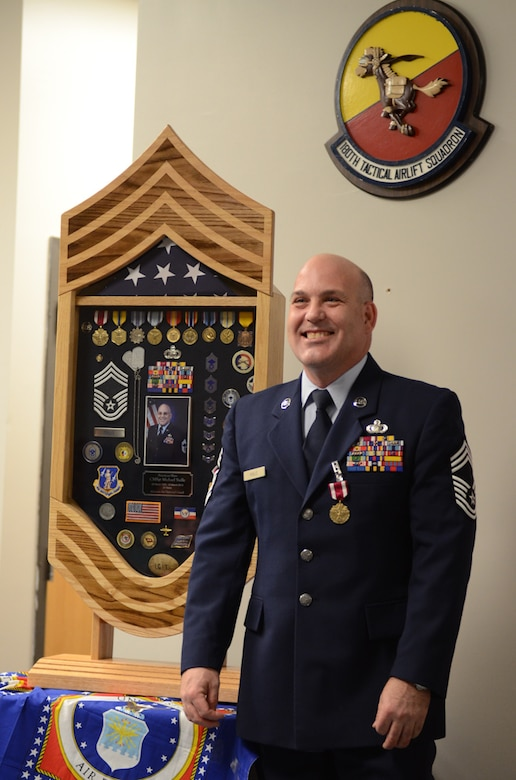 Chief Master Sgt. Mike Yuille, budget officer for the 139th Finance Office, stands next to his shadow box during his retirement ceremony March 5, 2013, at Rosecrans Air National Guard Base. (Missouri Air National Guard photo by Tech. Sgt. Michael Crane)