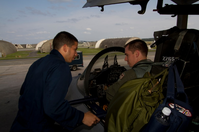 "Airman 1st Class Agustin Gonzales, 44th Fighter Squadron aircraft maintainer, performs final pre-flight checks with Capt. Jeffery Thomason, 44th FS pilot, before a mission on Kadena Air Base, Japan. Gen. Herbert Carlisle, Pacific Air Forces commander, recently announced Kadena's 44th FS ""Vampire Bats"" as winner of the Raytheon Trophy for 2012. (Courtesy photo by Jake Melampy)"