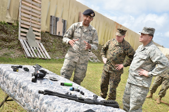 (Left) Staff Sgt. Jason Brown, 736th Security Forces Squadron Commando Warrior instructor, describes the different types of armament Airmen train with at the Pacific Regional Training Center to (center) U.S. Marine Corps Maj. Gen. James Kessler, commander, Marine Corps Installations Command, and (right) Maj. Gen. Timothy Byers, Air Force Civil Engineer, Headquarters U.S. Air Force, on Northwest Field, Guam, Feb. 27, 2013. The leaders toured base structures and developments to gain insight on successes and challenges within Joint Region Marianas. (U.S. Air Force photo Staff Sgt. Alexandre Montes/Released)