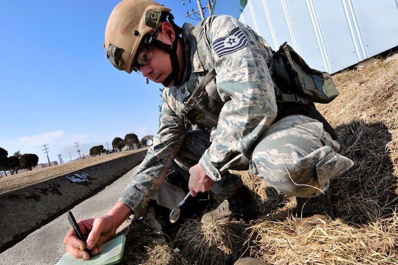 Tech. Sgt. Tobin Bryant, 51st Civil Engineer Squadron explosive ordnance disposal flight NCO in charge, records information about an unexploded ordnance in an exercise at Osan Air Base, Republic of Korea, Feb. 21, 2013. The information was then used to reference EOD databases to determine the proper protocol for disposal. (U.S. Air Force photo/Airman 1st Class Alexis Siekert)
