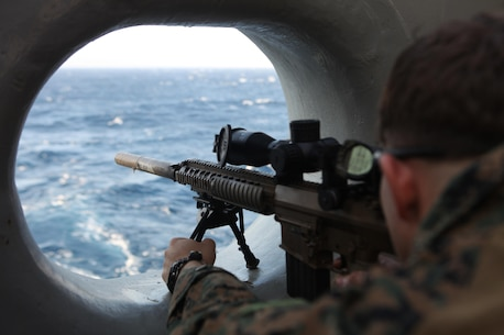 A Marine with the Maritime Raid Force, 31st Marine Expeditionary Unit, fires an M110 Semi-Automatic Sniper System rifle through a freeing port (a hole to allow water runoff) at a target from the stern of the ship here, March 6. The snipers of the 31st MEU's Amphibious and Force Reconnaissance Platoons conducted marksmanship training to keep their skills sharp for any contingency operation that they may be called upon to execute. The 31st MEU is the only continuously forward-deployed MEU and is the Marine Corps' force in readiness in the Asia-Pacific region.