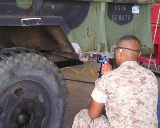 A Marine lance corporal in Okinawa, Japan, performs organizational-level surface preparation using the Corrosion Prevention and Control tool kit to remove corrosion prior to the application of touch-up paint on a trailer. The corrosion program, managed by Marine Corps Systems Command, has improved the readiness of USMC equipment and significantly reduced the cost of corrosion.