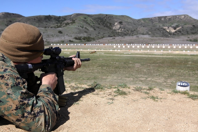 """Staff Sgt. Peter Anderson fires an M-4 service rifle during the Western Division Matches held at Wilcox Range here March 6.   """"The Marine Corps Shooting Team has been very helpful in adjusting my standing firing position,"""" said Anderson, the substance abuse control officer of 1st Radio Battalion here. """"This is my second year competing in the Division Matches."""""""