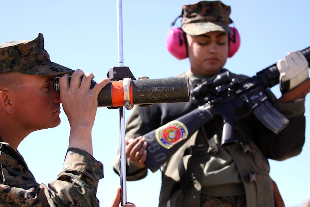 Sgt. Shayne Whitaker, left, reviews shot points for his teammate Cpl. Raquel Martinez while she waits on the firing line to continue shooting during the Western Division Matches held at Wilcox Range here March 6.   Whitaker is a block noncommissioned officer for Edson Range with Marine Corps Recruit Depot and Martinez is a range coach with MCRD.
