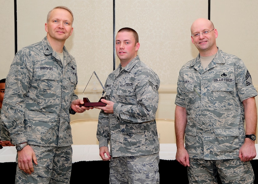 Colonel Darren Hartford, 437th Airlift Wing commander, and Chief Master Sgt. Gerard Komen, 437th Maintenance Operations Squadron superintendent, congratulate Senior Airman Joseph Shewmaker, 437th Operations Group knowledge operations manager, as a Diamond Sharp award winner during a ceremony March 5, 2013, at the Charleston Club at Joint Base Charleston - Air Base, S.C. Diamond Sharp awardees are Airmen chosen by their first sergeants for their excellent performance. (U.S. Air Force photo/ Staff Sgt. Rasheen Douglas)