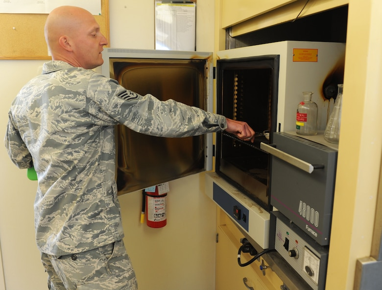Staff Sgt. Paul Bauer, 9th Civil Engineer Squadron water and fuels system maintenance journeyman, prepares to bake a sample of bio-solid in an oven set to 265 degrees Celsius at the waste water facility on Beale Air Force Base, Calif., March 5, 2013. Through this scientific process the facility is able to determine how much bacteria is being removed from the bio-solid. (U.S. Air Force photo by Airman 1st Class Bobby Cummings/Released)